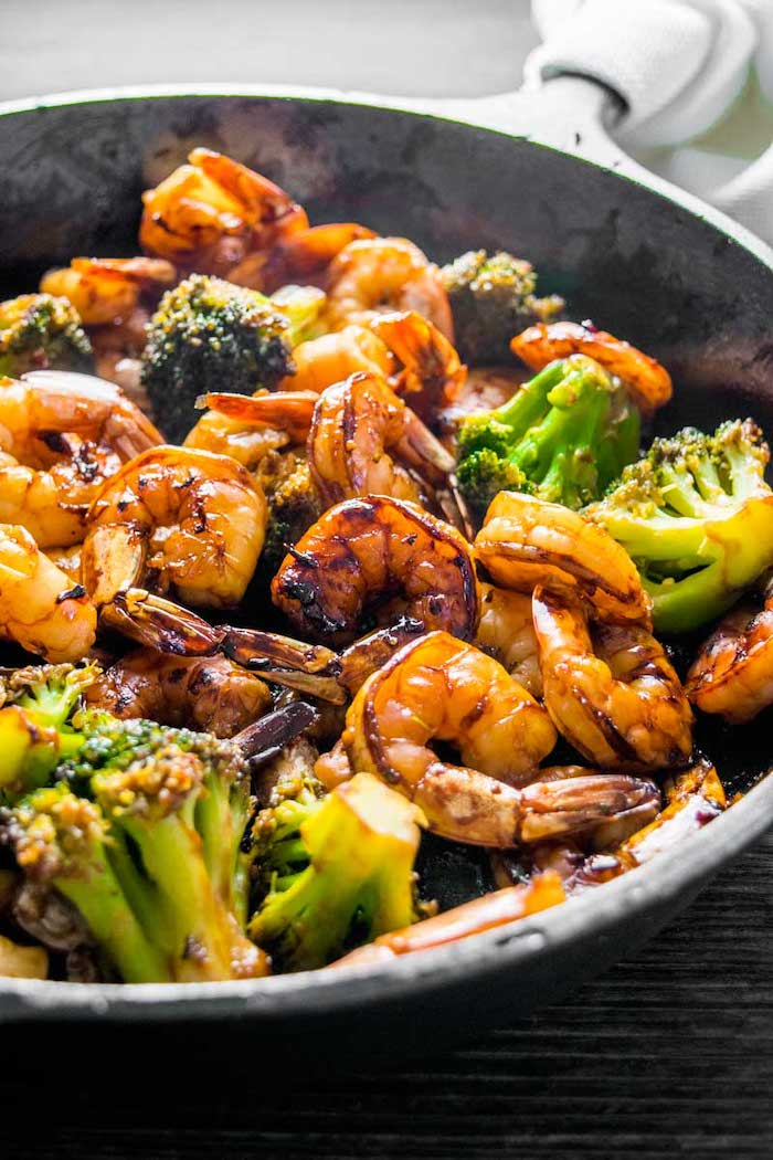 easy dinner recipes for beginners, honey garlic shrimp with broccoli, cooked in a skillet, black wooden table