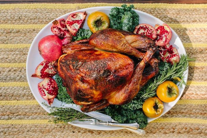 roasted turkey, how to cook a turkey in the oven, pomegranates and apples, fresh herbs, on the side