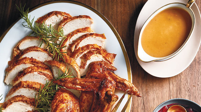 gravy in a jug, how to cook a turkey in the oven, turkey slices, fresh rosemary, in a white plate, wooden table