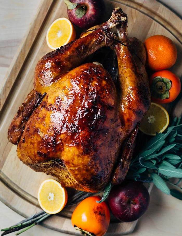 thanksgiving turkey recipe, roasted turkey, lemons and oranges, fresh herbs, on the side, wooden board