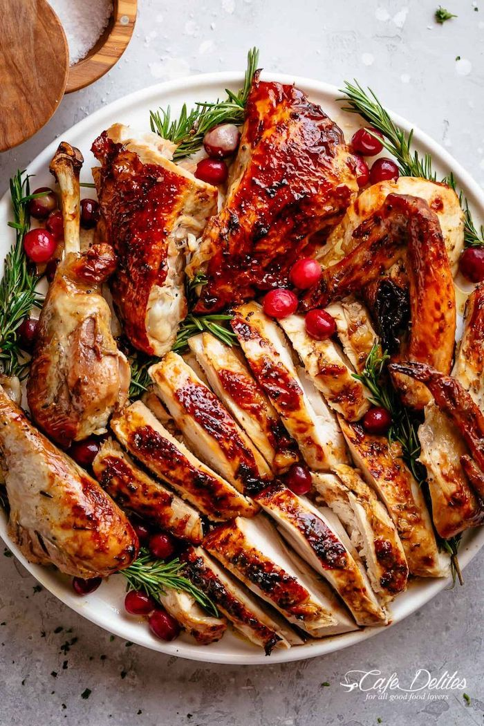 carved turkey, with cranberries, fresh rosemary, on the side, how long to cook a turkey, white plate, granite countertop