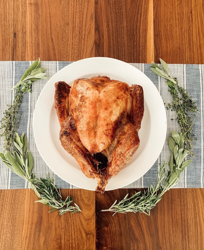 wooden table, white plate, roasted turkey, blue and white cloth, fresh herbs wreath, how to cook a turkey in the oven