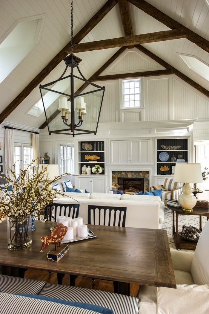 wooden dining table, white sofa, blue throw pillows, vaulted ceiling with beams, ceiling with skylights