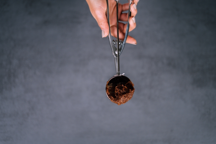 granite countertop, energy balls, female hand, with grey nail polish, holding and ice cream scoop, with chocolate mixture