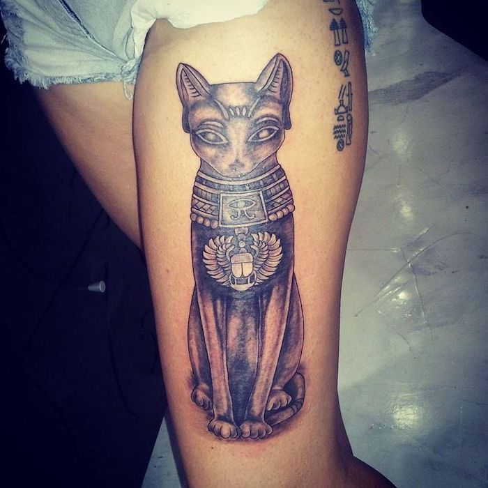 leg tattoo ideas, sacred egyptian cat, denim shorts, white floor