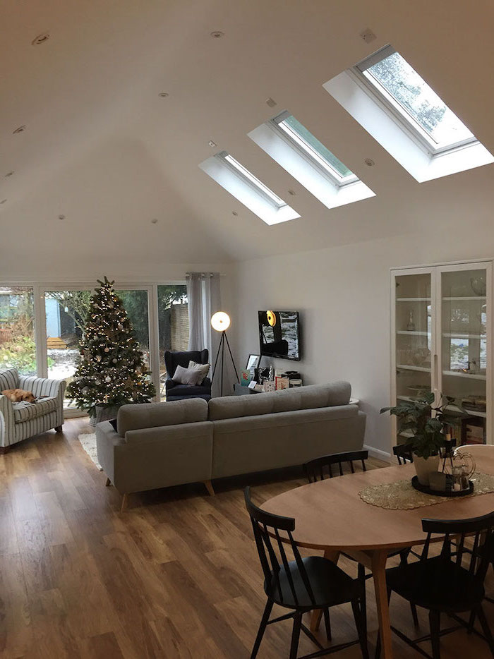 white ceiling with skylights, grey sofa, christmas tree, what is a vaulted ceiling, wooden floor, wooden table