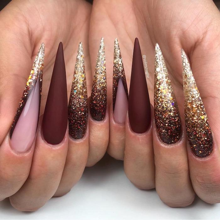 red burgundy, matte nail polish, gold glitter, long stiletto nails, white background, fall nail ideas