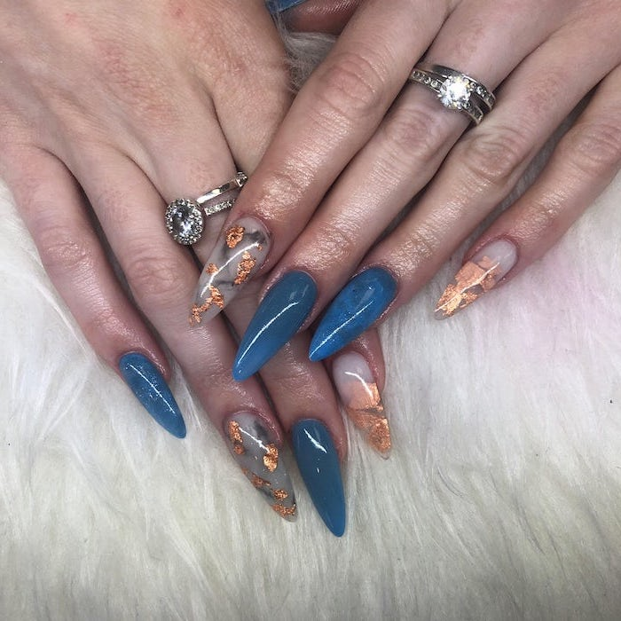 long stiletto nails, blue nail polish, gold glitter, nail decorations, autumn nails, silver rings