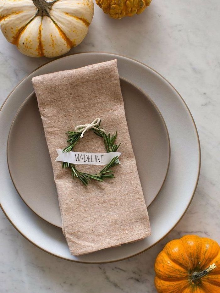rosemary wreath, over napkin, madeline table setting, outdoor thanksgiving decorations, white plates, marble countertop
