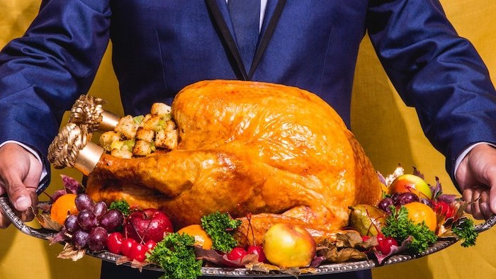 how to prepare a turkey, man in a blue suit, carrying a silver tray, wit stuffed turkey, fruits and herbs on the side