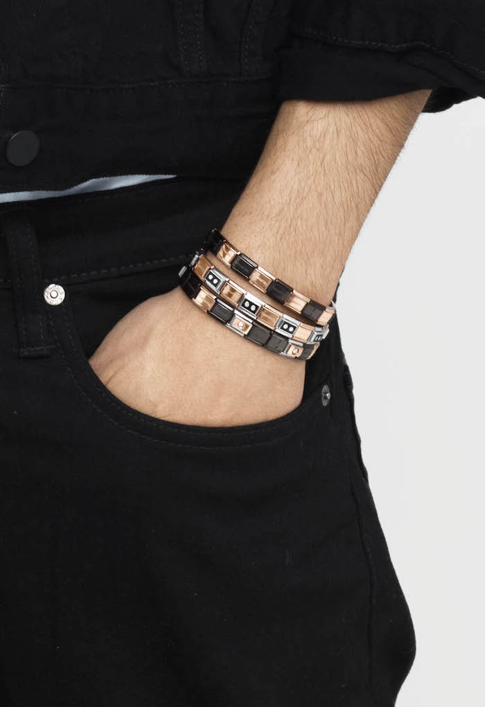 christmas gift ideas, man with black jeans, black denim jacket, hand in pocket, three bracelets