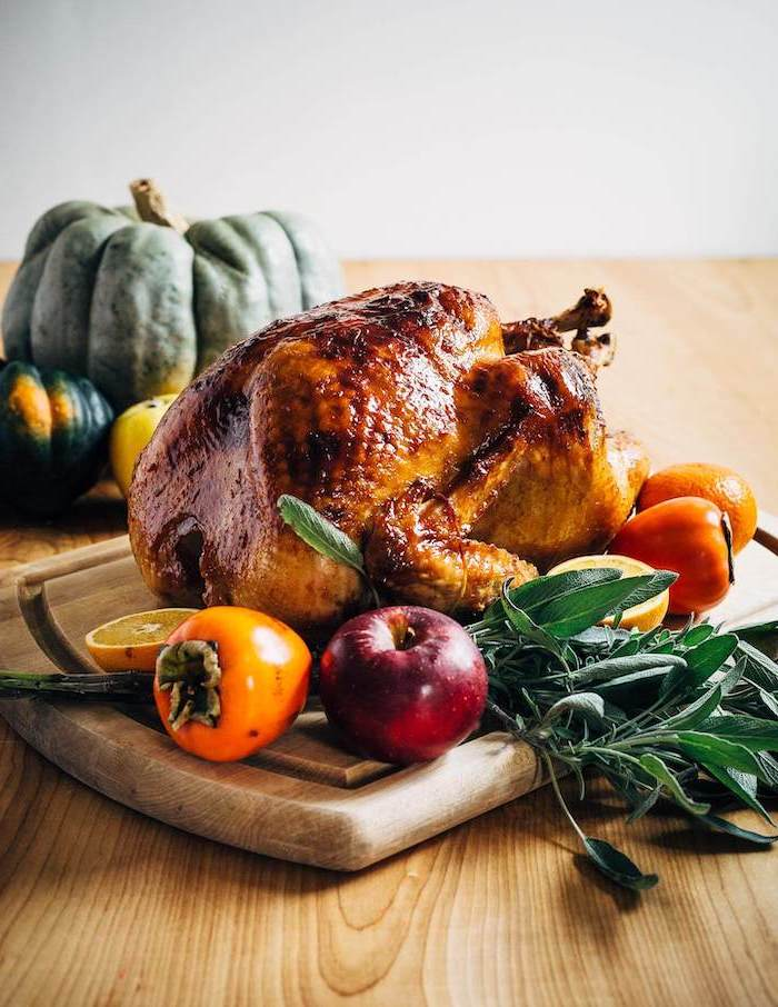 roasted turkey, thanksgiving turkey recipe, apples and tangerines, fresh herbs, wooden board, wooden table
