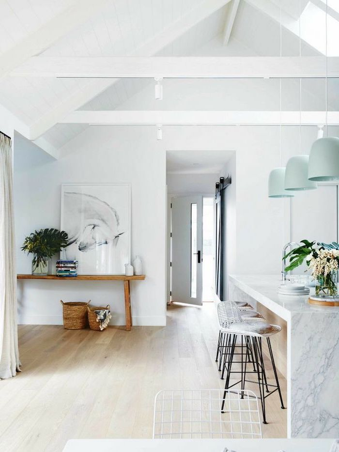 hanging blue lamps, over marble kitchen island, bar stools, what is a vaulted ceiling, wooden floor, white walls