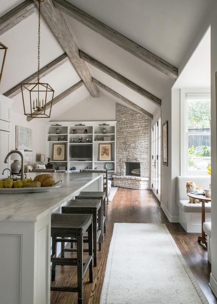 stone fireplace wall, marble kitchen island, what is a vaulted ceiling, wooden floor, grey wooden beams