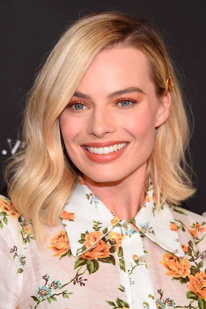 margot robbie smiling, blonde wavy hair, side swept, hairstyles for women, wearing white floral shirt