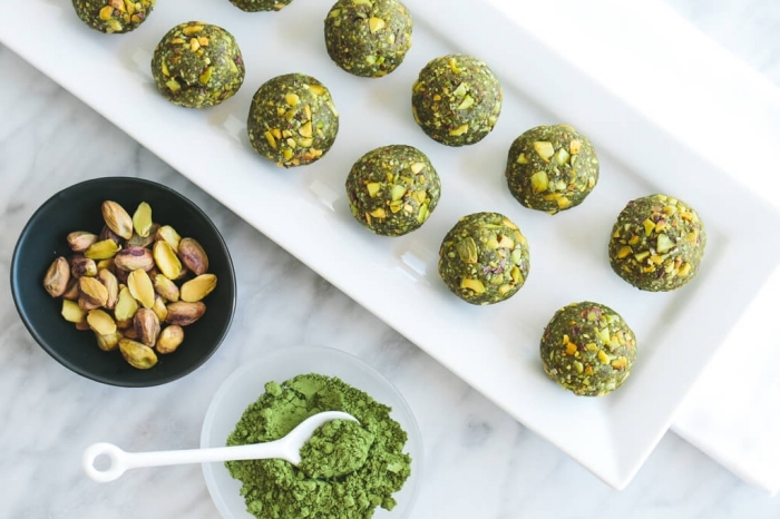 matcha powder, pistachio nuts, in two bowls, energy bites recipe, arranged on white plate, marble countertop