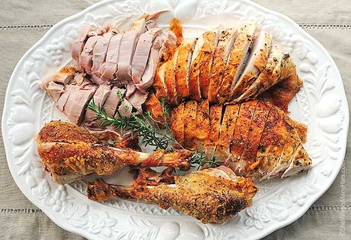 carved turkey, in a white plate, fresh rosemary, on the side, what temperature to cook a turkey