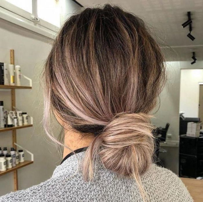 shoulder length hairstyles, balayage blonde hair, in a low chignon, woman wearing grey sweater