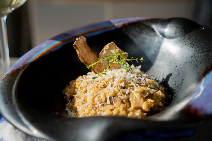 mushroom risotto recipe, placed in black bowl, topped with parmesan and fresh thyme