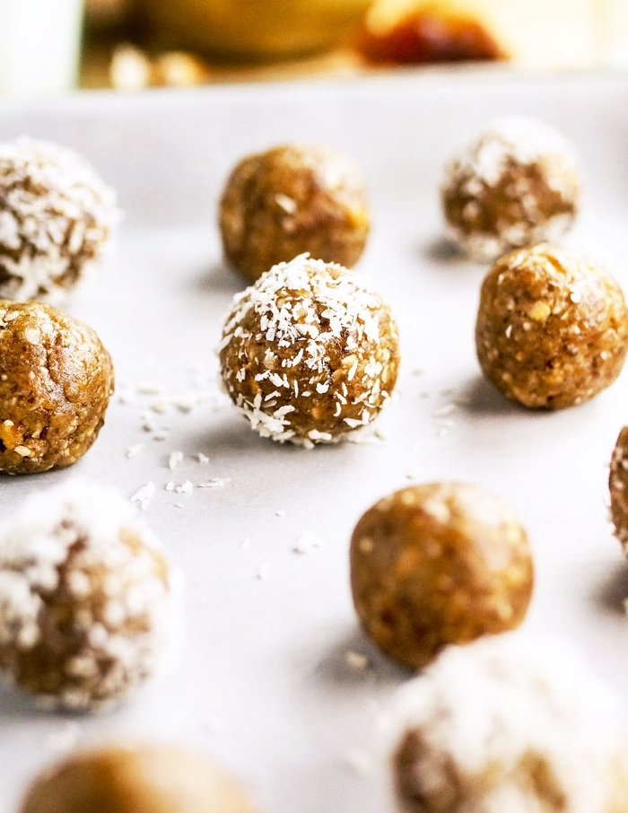 date energy balls, peanut butter bites, covered with coconut flakes, on baking paper