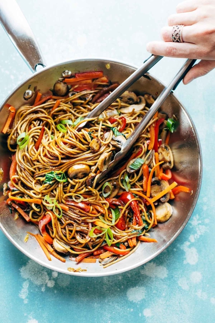noodles with mushrooms, peppers and onion, cooked in skillet, easy dinner recipes for beginners, with tongs inside