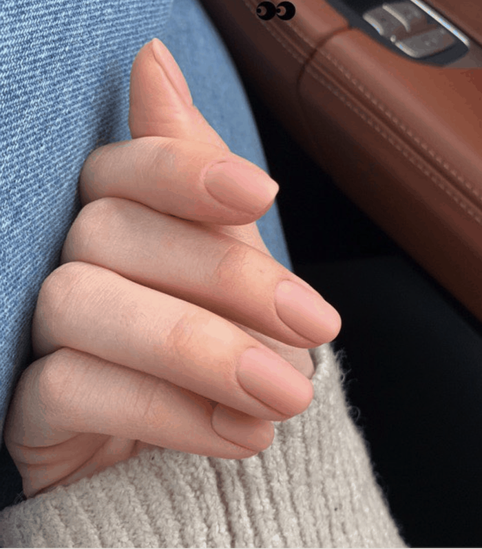 nude nail polish, cute fall nails, hand resting on a leg, white sweater, brown leather, in the background