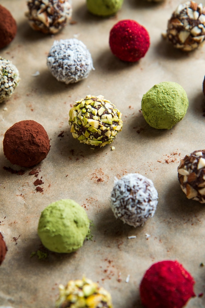 date energy balls, arranged on baking paper, covered with cocoa, coconut flakes, nuts and matcha powder