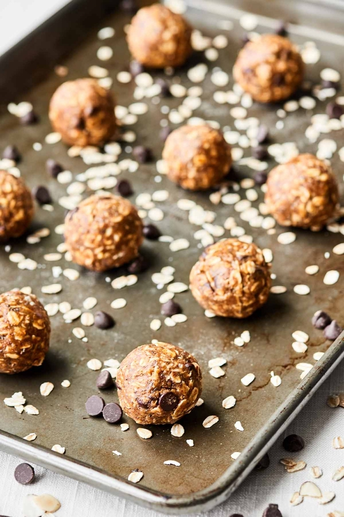 chocolate chips and oatmeal, scattered around, date energy balls, arranged in a sheet pan