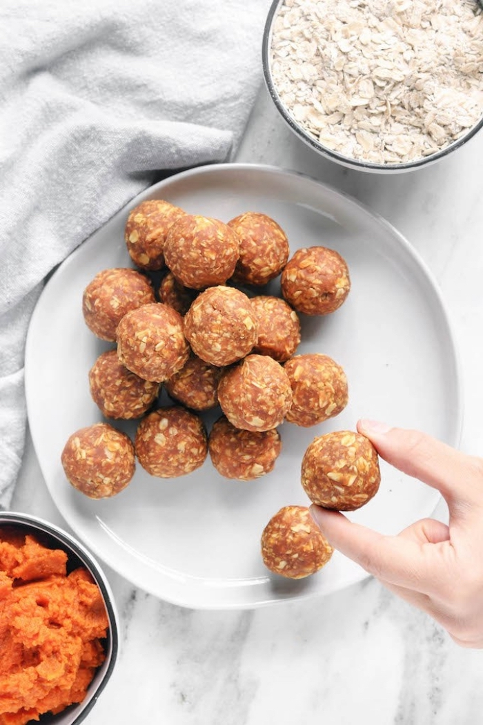 peanut butter oat balls, oatmeal in a bowl, squashed carrots in a bowl, white plate, marble countertop