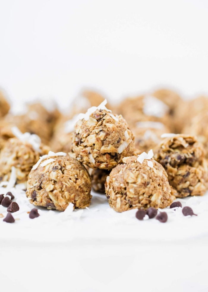 oatmeal balls, peanut butter oat balls, with chocolate chips, coconut flakes, on white table