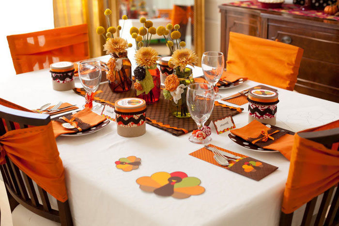 wooden chairs, orange ribbons on them, pinterest thanksgiving, flower bouquets, plate settings, white table cloth