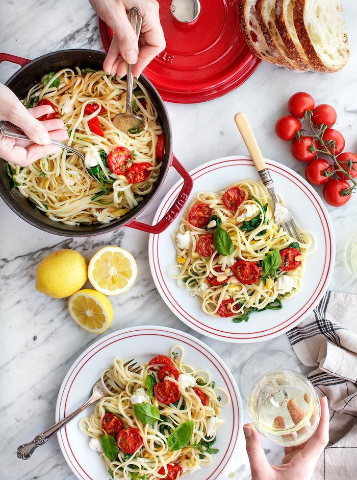 pot full of pasta, pasta in two white plates, with tomatoes and mozzarella, basil leaves for garnish, easy dinner ideas