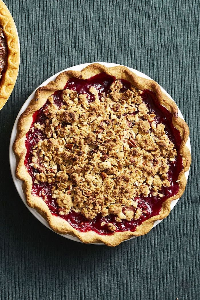 pear and blackberry pie, crushed nuts on top, white plate, dark grey cloth, thanksgiving cake ideas