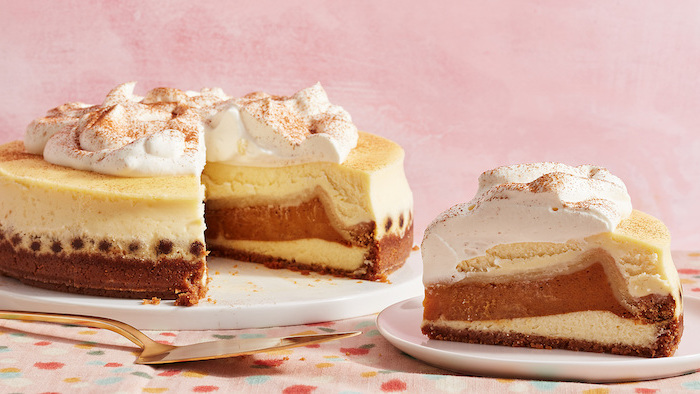 three layers, slice of cake, cream and cinnamon on top, thanksgiving cake ideas, white plates