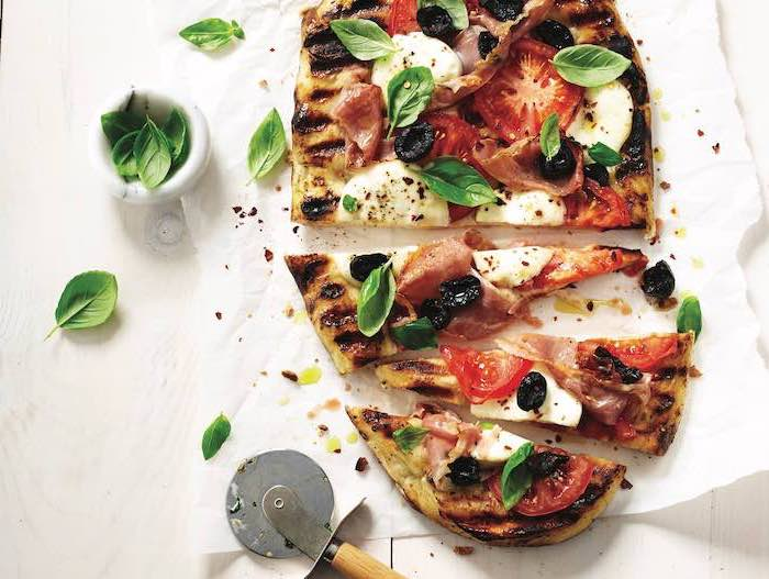 grilled pizza, with mozzarella, tomatoes and olives, basil leaves on top, what to make for dinner tonight, cut into pieces