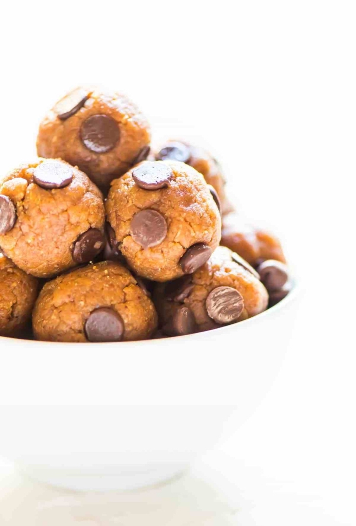 chocolate peanut butter protein balls, with chocolate chips, in a white bowl, white background