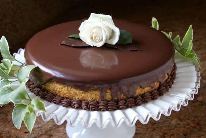 best thanksgiving desserts, pumpkin cake, chocolate glaze, on white cake stand, white rose on top