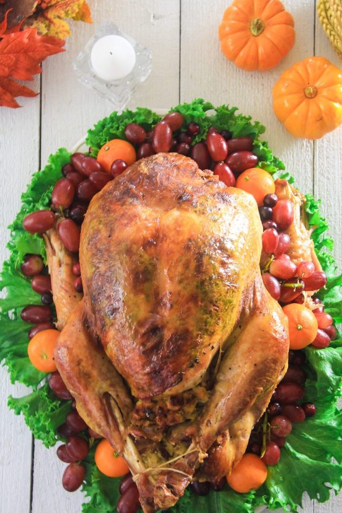 white wooden table, how to prepare a turkey, roasted turkey, on top of green salad, pumpkin decorations