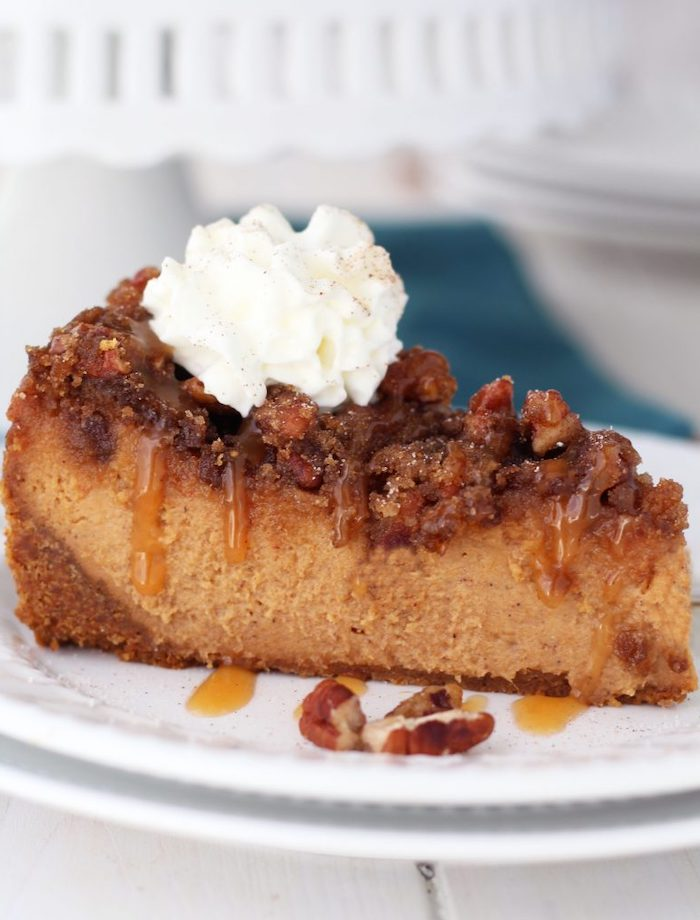 slice of cake, pecan cheesecake, thanksgiving dessert recipes, caramel drizzle, cream on top, white plate