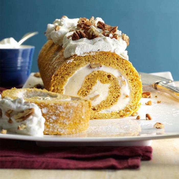 pumpkin pie roll, thanksgiving desserts for kids, cream and walnuts, powdered sugar, on top, white plate