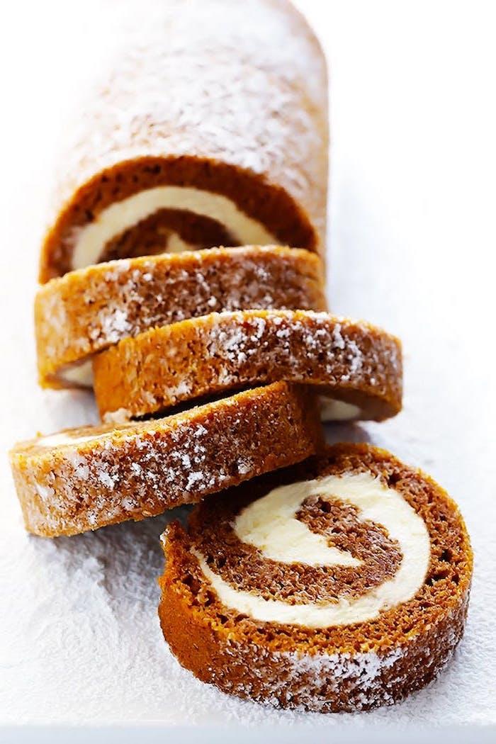 pumpkin pie roll, white frosting inside, thanksgiving desserts for kids, powdered sugar on top