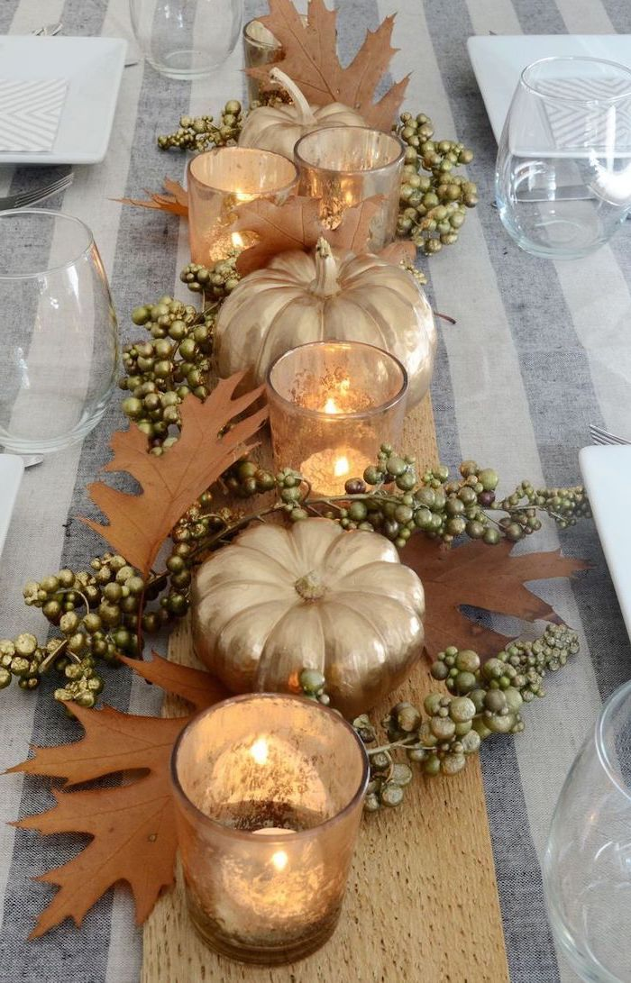 gold pumpkins, fall leaves, candles arranged, in the middle of the table, thanksgiving door decor, water glasses