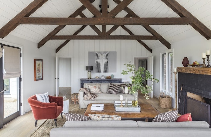 red velvet armchair, how to vault a ceiling, white wooden walls, wooden beams, white sofas, black brick fireplace
