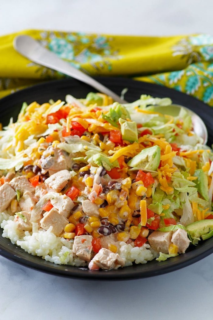 rice with chicken, corn and avocado, cheese and tomatoes, in black bowl, what to make for dinner tonight, spoon on the side