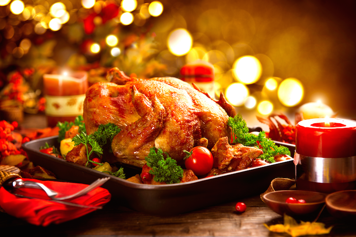 how to cook a thanksgiving turkey, wooden table, christmas candles, red cloth, roasted turkey, in a black pan