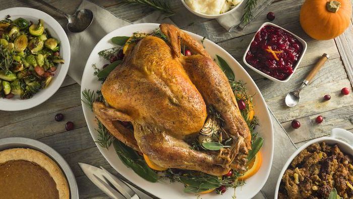 cranberry sauce, wooden table, roasted turkey, fresh herbs, lemon slices, on the side, how to cook a thanksgiving turkey