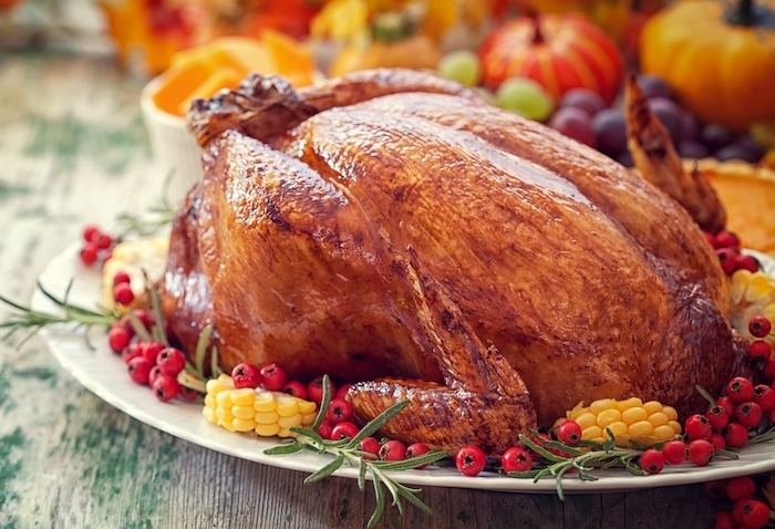roasted turkey, corn and cranberries, on the side, how to cook a thanksgiving turkey, white plate, wooden table