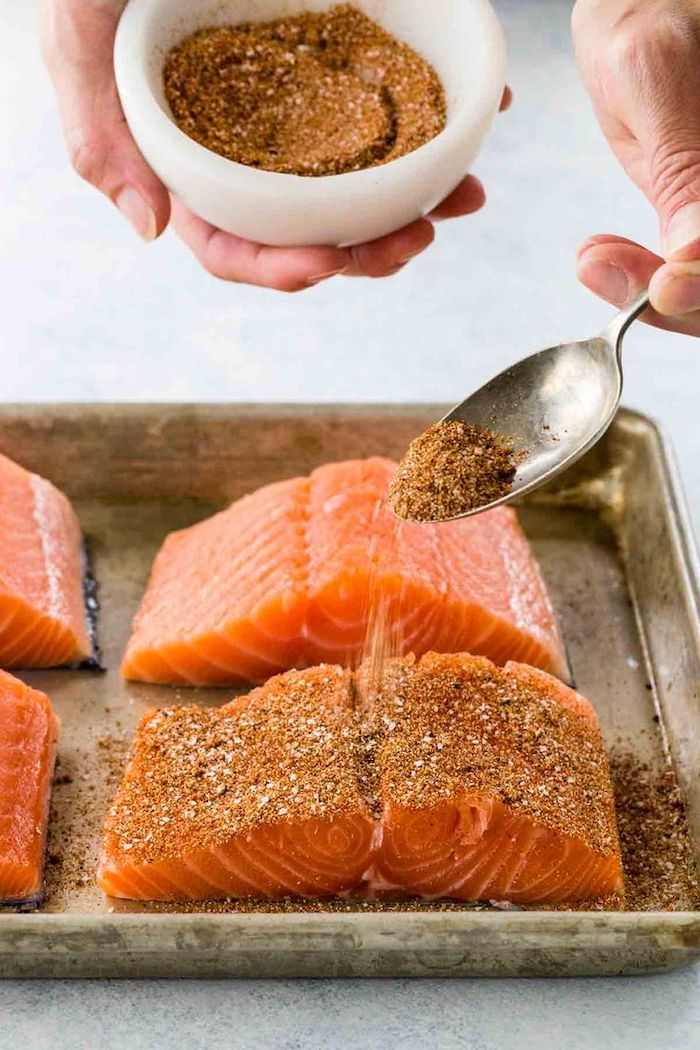 salmon fillet, seasoned with dry herbs, out of a white bowl, with a spoon, low calorie meals, sheet pan