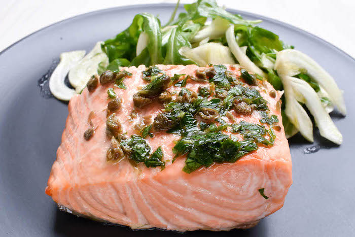 simple meal plan to lose weight, salmon fillet, herbs sauce on top, salad on the side, black plate