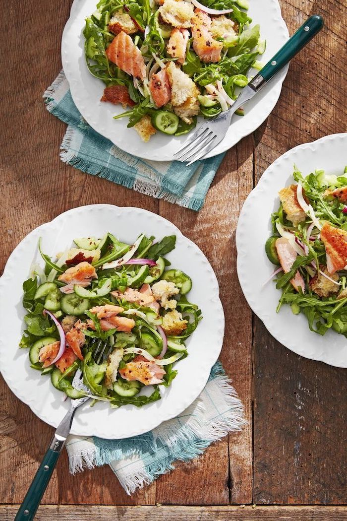 wooden table, healthy dinners for two, white plates, salmon panzanella inside, forks on the side, blue and white table cloths